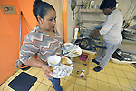 Begum Ali carries dirty dishes while her husband Moshaid washes up in the small restaurant they run in Budapest, Hungary. Refugees from Bangladesh, they came to Hungary in 2013, were granted refugee status, and opened the restaurant in 2014.<br /> <br /> As Hungary dealt with a massive flow of new refugees in 2015, the country wrestled with its responsibility to the newcomers. Yet old-timers like the Ali family report they have felt welcomed during the years they have lived in Hungary.