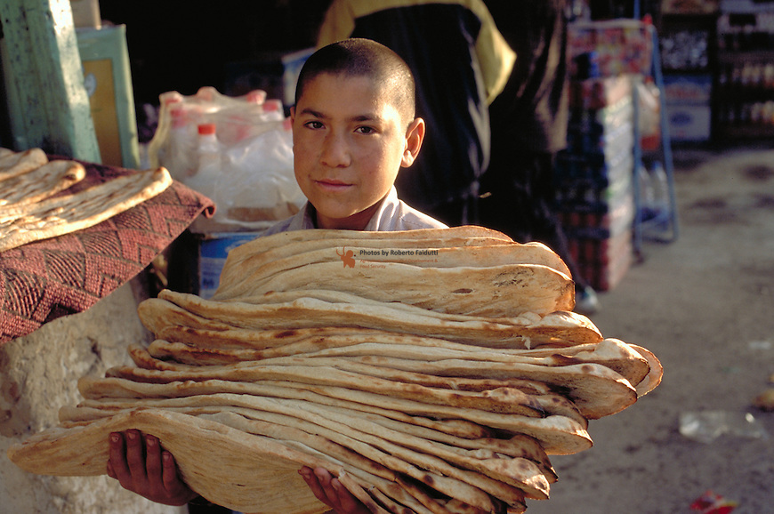 youg boy carrying traditional afghan bread for selling