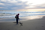 Prospector with metal detector searching for buried treasures at Santa Monica beach