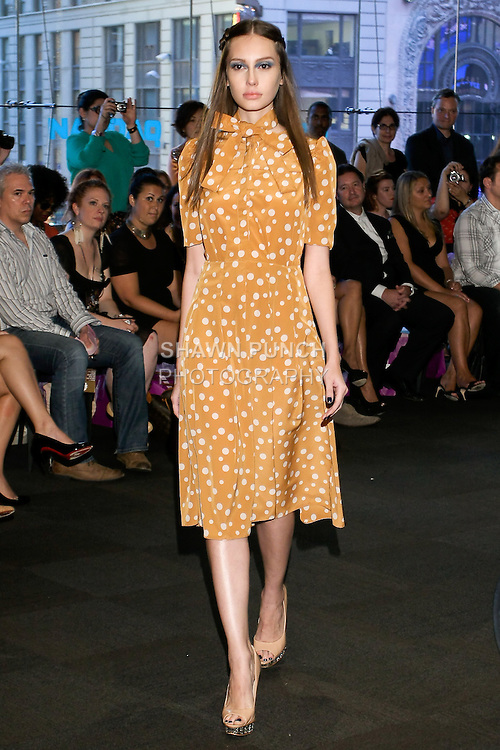 """Model walks runway in a beige polka dot dress, from the Yuna Yang Spring Summer 2013 """"Close your eyes and see the world"""" collection, at the NASDAQ Marketsite, during New York Fashion Week, on September 7, 2012."""