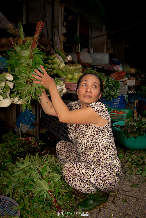 Grocers preparing leafy vegetables for the afternoon sales, in Ben Thanh Markets, Ho Chi Minh City Vietnam.