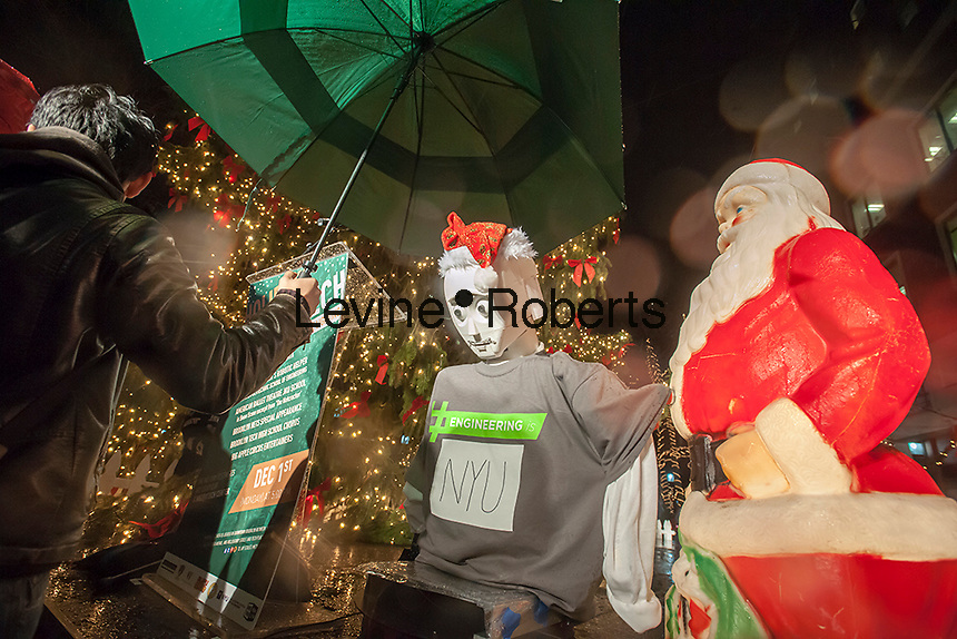 Caesar the robot pushes the switch to light the MetroTech Christmas tree at their 25th annual tree lighting in Brooklyn In New York on Monday, December 1, 2014. Caesar, Cellularly Accessible Expressive Semi-Autonomous Robot, was created by the NYU Mechatronics Lab. Caesar is built with off the shelf and 3d printed parts, using the Linux operating system and was created by Jared Frank and a team of engineering students at NYU-Poly and is very cost effective. (© Richard B. Levine)