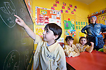 Rafeba Hussein looks on as a boy solves problems on the chalkboard in a school in the Sabra refugee camp in Beirut, Lebanon, run by the Department of Service for Palestinian Refugees of the Middle East Council of Churches. Most of the school's 148 students are Syrian refugees, but roughly one-third are Palestinian refugees and a few are poor children from the neighborhood. Lebanon hosts some 1.5 million refugees from Syria, and yet the government prohibits the establishment of large refugee camps, thus pushing many refugee families to search for housing in existing Palestinian refugee camps. This school is supported by the ACT Alliance.