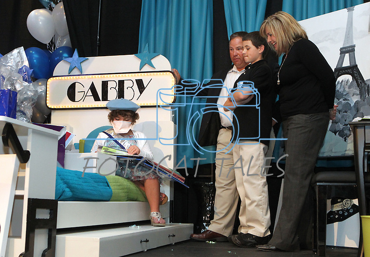 Gabby Gouldsmith, 8, her parents Buddy and Heather, and brother Garrett, check out her new bedroom makeover during the Make-A-Wish Foundation Waffles & Wishes event at the Atlantis Casino Resort, in Reno, Nev., on Tuesday, March 27, 2012. Gouldsmith, who suffers from an auto-immune deficiency disorder, was recognized at the event. .Photo by Cathleen Allison