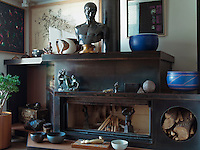 In the living room the iron/epoxy fireplace was designed by Hakan Ezer.  Vases by Alev Ebuzziya Siesbye are displayed on the mantelpiece beside a bronze bust, and the paintings, left to right, are by Nejat Devrim, Mehmet Guleryuz and Komet
