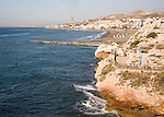 Coastline with breakwater groyne, waves and beach at La Cala del Moral, Malaga, Spain