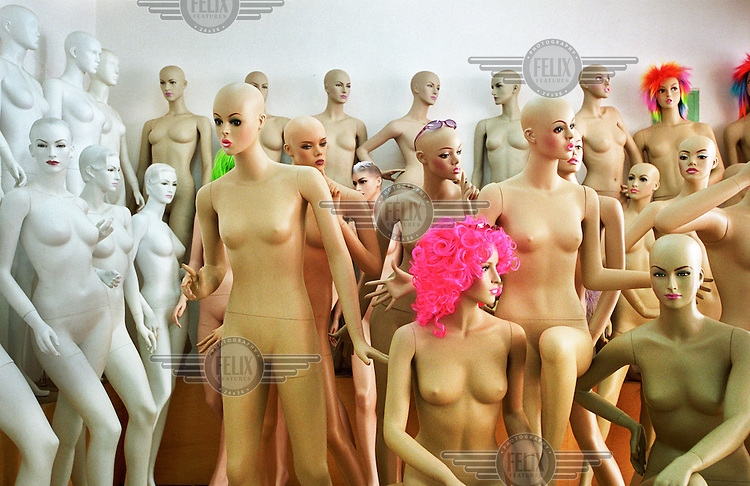 Plastic mannequin models with wigs stand in a shop.