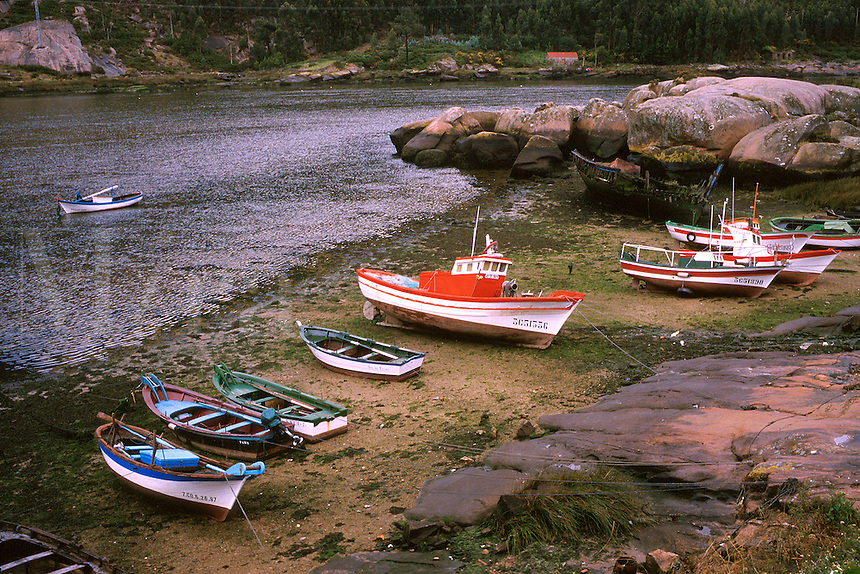 Spain, Galicia, Ezaro. Beached fishing boats at low tide in a protected inlet. Costa de morte, death coast.