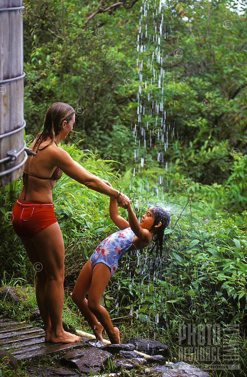Mother and daughter showering in rainwater waterfall from reservoir along  Maunawili trail, windward Oahu