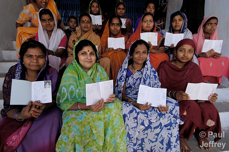 Women in Hyderabad, India, show their savings passbooks. They participate in a self-help group where they save their money and then loan it out to each other at terms they designate.