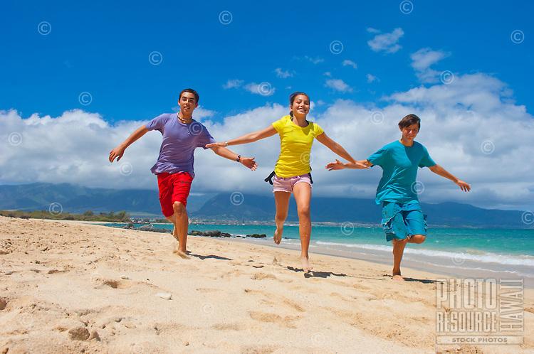 Teens running on beach at Kanaha Beach Park, Kahului, Maui