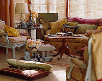 The sofa is upholstered in a faded chintz and the chair in a 19th century kilim surrounded by a profusion of Moroccan and Indian cushions
