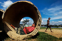 A man lay in a tube and checks his mobile, as an elderly man walks past in Dhaka, Bangladesh.