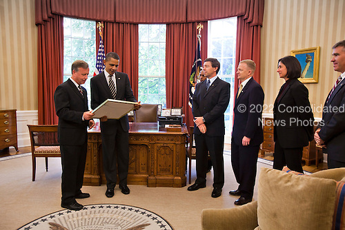 United States President Barack Obama accepts a photograph from Space Shuttle Discovery Commander Steve Lindsey as the rest of the Discovery crew looks on in the Oval Office of the White House in Washington, DC, USA, on 09 May, 2011..Credit: Jim LoScalzo / Pool via CNP
