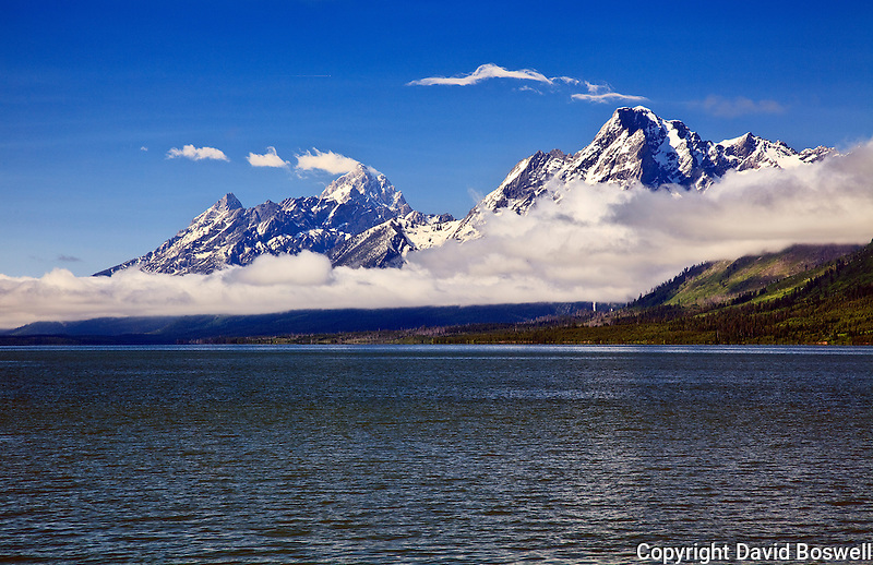 Grand Teton (left) and Mount Moran (right) soaring above the morning clouds, with Jackson Lake in the foreground.