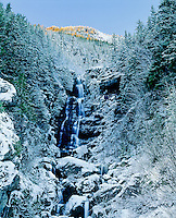 Ketchum Creek waterfalls in winter with larch trees in late fall color highlighting a ridgeline above. North Cascades National Park, Washington State