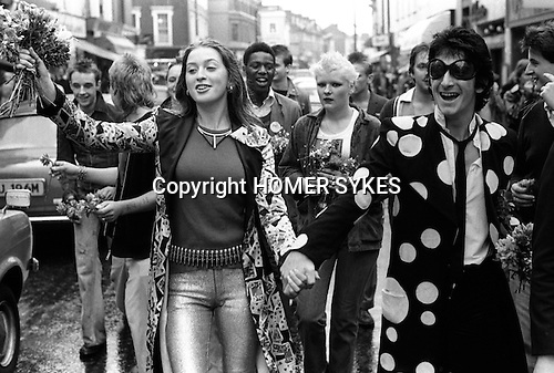 Punks hand out flowers to passing car drivers as they walk down the middle of the Kings Road, Chelsea, London. England. 1977. Tracy Boyle girlfriend of  Gary Holton lead singer with Heavy Metal Kids, who went on to play Wayne in the UK television comedy Auf Wiedersehen, Pet.