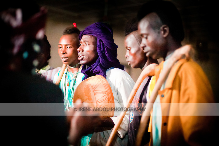 """In the town of Djibo in northern Burkina Faso, young """"doohoobe"""" (people who sing """"doohaali"""") dance in traditional fashion. The men and women each form a line facing each other, rhythmically shuffling towards and then away from each other. The women clap their hands and sing as the men """"dooho,"""" or sing a distinct, deep rhythmic chant. The man in the purple turban plays a calabash (a form of drum), as the other men hold """"cabbi,"""" sticks which are used when herding cattle. """"Doohaali"""" is a distinct form of music practiced only by the Fulani in Djelgooji, a particular area of Burkina Faso. The young men in this image are the winners of a regional music and arts competition, going on to perform at Burkina Faso's 2010 """"Semaine Nationale de la Culture"""" (SNC) in Bobo-Dioulasso.  The women clapping at left are members of the community who have joined in the nighttime fun."""