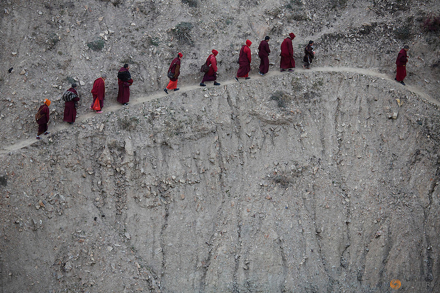 Monks and nuns walk across a steep hill back to their dormitory after attending a daily chanting session during the Utmost Bliss Dharma Assembly, the last of the four Dharma assemblies at Larung Wuming Buddhist Institute in remote Sertar county, Garze Tibetan Autonomous Prefecture, Sichuan province, China early November 1, 2015. The eight-day gathering of people chanting mantras and listening to teachings of monks starts every year around the 22rd of the ninth month on Tibetan calendar, the great day of Buddha's Descending from Tushita Heavens. The Larung Wuming Buddhist Institute, located some 3700 to 4000 metres above the sea level was founded in 1980 by Khenpo Jigme Phuntsok, an influential lama of Nyingma sect of Tibetan buddhism with only around 30 students but is now widely known as one of the biggest centres to study Tibetan Buddhism in the world. Picture taken October 30, 2015.  REUTERS/Damir Sagolj