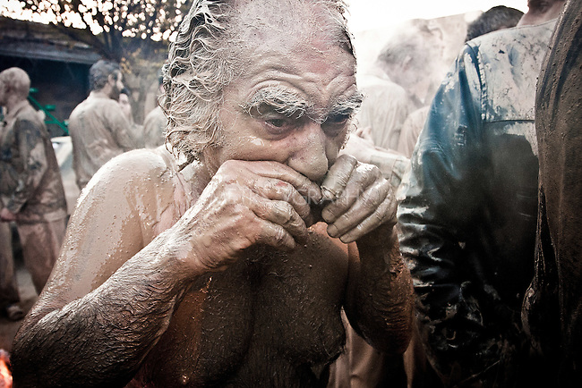 KHORRAMABAD, IRAN : A man covers his mustache in mud during the festival of Ashura...Every year to mark the death of Imam Hussein, Shia Muslims mourn for two days. In Khorramabad and Lorestan in the west of Iran, during the first day of mourning, called Tasooa, women take a vow of silence and go through the streets with the children lighting candles. At 4 am on Ashura, the second day, men cover themselves in mud and then stand in front of a fire until the mud has dried to clay. After this they go to the mosque and pray...Photo by Farhad Babaei/Metrography