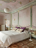 A double bed with a white cover stands in a pink and green bedroom with traditional painted decoration on the walls and ceilings. A modern lamp stands on an Eero Saarinen bedside table.