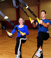 Cheryl Langrehr and John Ernst demonstrate the TRX suspension trainer at Harbor Athletic Club in Middleton on Wednesday, 12/31/08