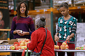 """United States President Barack Obama's daughters Malia Obama (L), 15 and Sasha Obama, 12, help pack and distribute bags of food to needy children and seniors at the Capital Area Food Bank November 27, 2013 in Washington, DC. According to the White House, the first family was joined by family and friends and members of The Mission Continues, """"an organization of post-9/11 veterans who are awarded community service fellowships."""" <br /> Credit: Chip Somodevilla / Pool via CNP"""