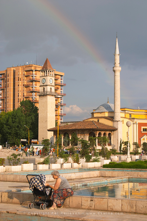 The Ethem Bey Beu Mosque. A woman sitting on the ledge of the fountain with a pram. The Tirana Main Central Square, Skanderbeg Skanderburg Square. Tirana capital. Albania, Balkan, Europe.