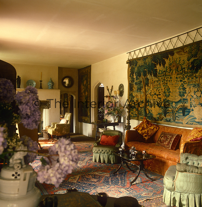 The wall of the hall at Nymans is hung with an antique tapestry and the room is furnished with a variety of comfortable seating