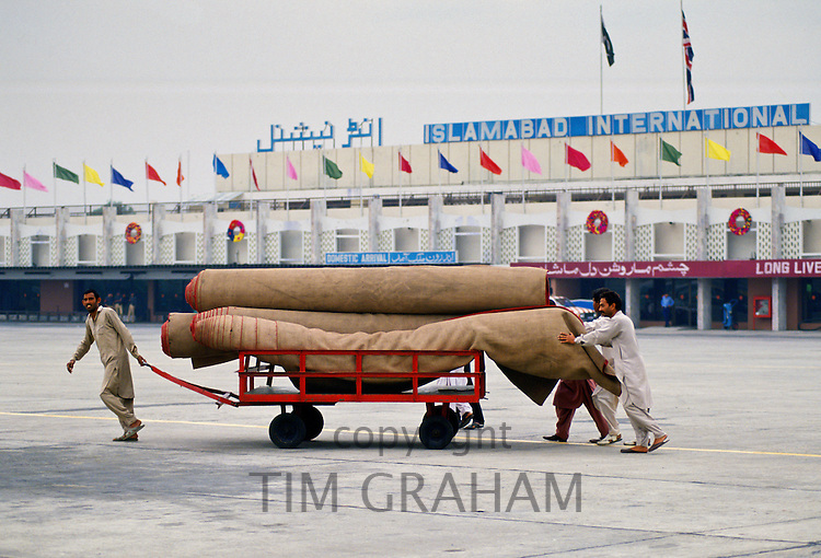 Men wheeling rugs at Islamabad airport, Pakistan. RESERVED USE - NOT FOR DOWNLOAD -  FOR USE CONTACT TIM GRAHAM