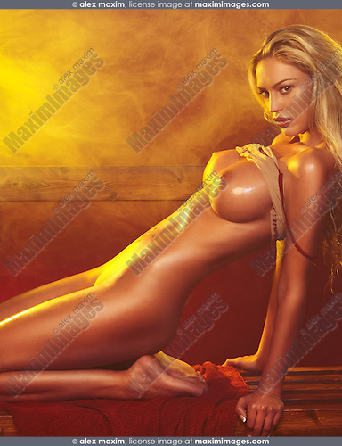 Artistic erotic photo of a beautiful nude woman with long blond hair posing in a steam room