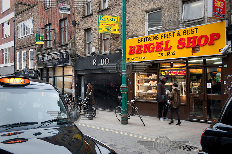 A taxi drives past a beigel (bagel) shop on  Brick Lane in Shoreditch, London.