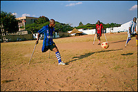 "Angola, May 2006.A match between the top 2 teams in the Angola handycapped football championship.""3 de Decembre"" (Disability Day, in red ) plays against ""11 de Novembre"" (Angola Independence Day, in blue).  Just 4 years after the end of a 25 year long civil war, Angola is starting to emerge again, yet a lot remains to be done: entire regions are still cut-off from the ouside world because of landmines and broken bridges, over 80% of the population lives below the poverty threshold in one of the potentially richest country in Africa. Natural ressources include oil, diamonds, gold and...water!.Malaria, tuberculosis, HIV/Aids are endemic, cholera and meningitis frequent."
