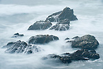 Point Arena, California; waves crashing over rocks along the coast near the Point Arena Lighthouse at dusk