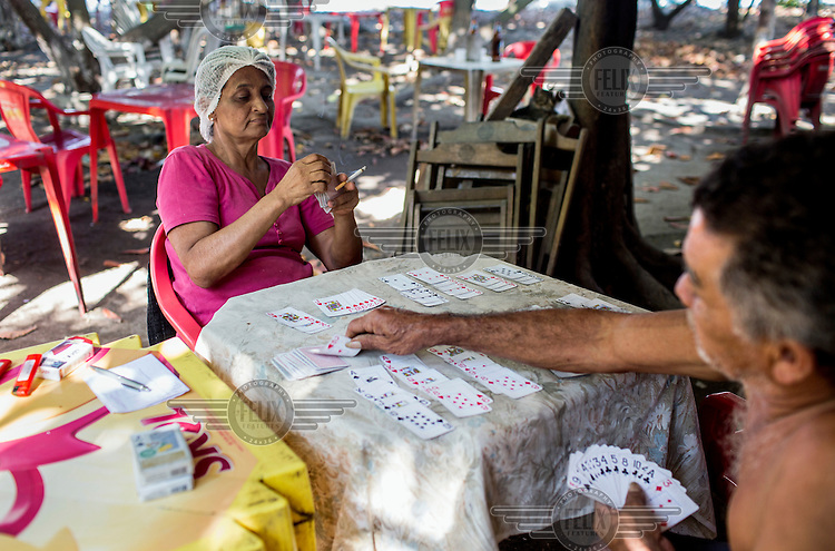 Tania Costa, 56, plays cards with a neighbour in her bar and restaurant in Jacrepagua.