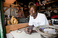 """""""I see the momentum of my business building quickly, soon you will find me in a modern structure as my shop,"""" said Peter Ogweno (R) , 32. He opened his electronics repair shop in Nairobi's Kibera slum in 2008 after working as an apprentice at a competitor's shop."""