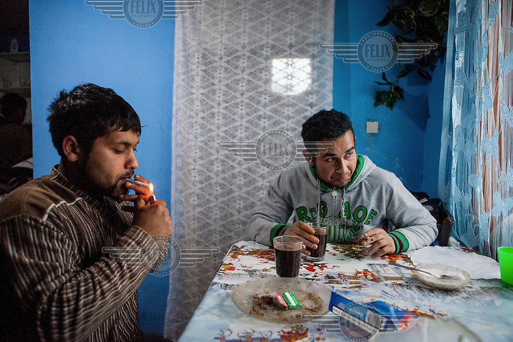 Michal (22) and Emil (20) having a coffee and cigarettes in Emil's newly built the new house which was funded by a micro-loan aimed at the local Roma community.