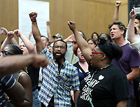 Protestors chant after shutting down the Charlottesville City Council meeting Monday night in Charlottesville, Va. Photo/Andrew Shurtleff