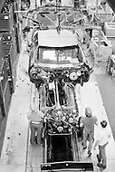 March 1973, Lansing, Michigan, USA --- Car assembly line at the Oldsmobile factory which was bought in 1908 by General Motors. 20,000 employees churn out 91 vehicles every hour, 16 hours a day, 5-6 days per week, according to demand. The lunch break lasts 30 minutes and is normally taken within the factory complex. Safety glasses are obligatory. --- Image by © JP Laffont