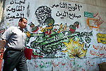 A Palestinian walks next to graffiti outside the Islamic university in Gaza Strip, July 9, 2003.  Municipal workers started to paint over graffiti in Gaza City. Photo by Quique Kierszenbaum.