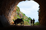 A couple walk through the tunnel at Zingaro Nature Reserve, Scopello, Sicily. The tunnel is a monument and symbol to people power - built as part of a road along this section of coast, local people protested, and the area was declared Sicily's first nature reserve.