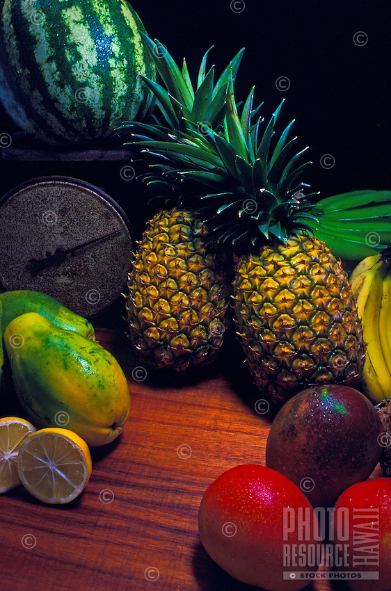 A close-up of a grouping of tropical fruits on a koa wood table.