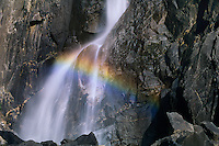 799451470 intimate detail of a waterfall where the light on the water flowing over granite rocks creates a rainbow at the base of yosemite falls in yosemite national park california