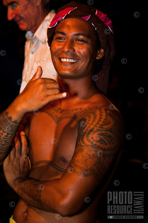 Tahitian man with traditional tattoos displays a big smile and a shaka