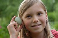 Mädchen, Kind lauscht an Hühnerei, Ei, um zu hören, ob das Küken sich schon bewegt und bald schlüpfen wird