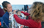 Volunteers wrap insulating material around a shivering refugee child on a beach near Molyvos, on the Greek island of Lesbos, on October 30, 2015. The child was on a boat full of refugees that traveled to Lesbos from Turkey, provided by Turkish traffickers to whom the refugees paid huge sums.