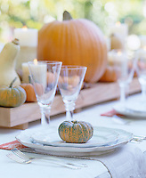 A miniature pumpkin is used as a place setting in this autumn inspired table decoration