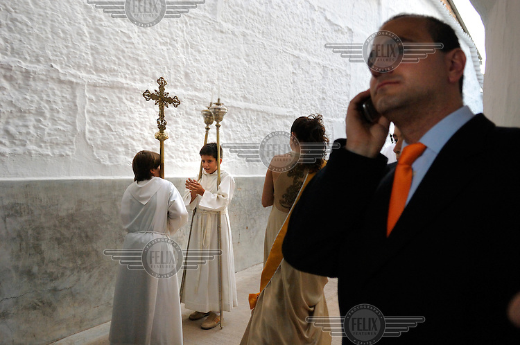 At the end of a religious procession through Campo de Criptana a church offical makes a mobile phone call as two altar boys talk together in the background..