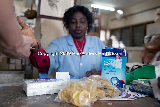 BAMENDA, CAMEROON - AUGUST 6: A customer buys imported milk powder from Europe in a super market on August 6, 2009 in Bamenda, Cameroon. Many small farmers in the area are struggling to cope with low milk prices, expensive inputs and competing with low priced milk powder that is heavily subsidized by European governments and dumped on international markets such as in Africa. The German company Oldenburger has just started selling powder milk and long life milk on the country, and they have hired many people to market their products on the streets. (Photo by Per-Anders Pettersson)....