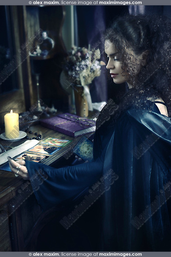 Portrait of a Beautiful mysterious woman fortune teller reading Taror cards at a table, Tarot card reader, devination artistic concept